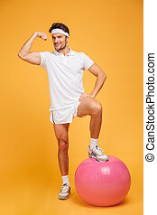 Young handsome sportsman with fitness ball showing biceps