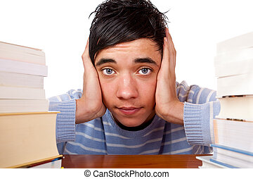 Young handsome student sitting on a desk between study books and looks frustrated. Isolated on white.