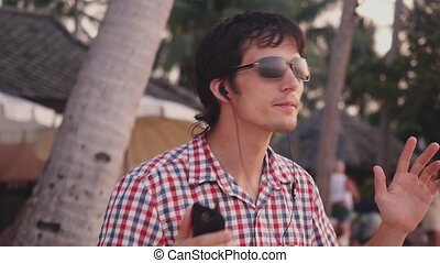 Young handsome stylish man in sunglasses listen to music and dance on tropical beach at sunset time. Slow motion. 1920x1080