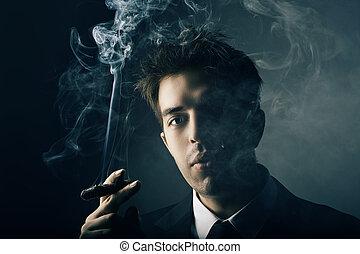 Young handsome stylish man smoking cigar, Fashion portrait