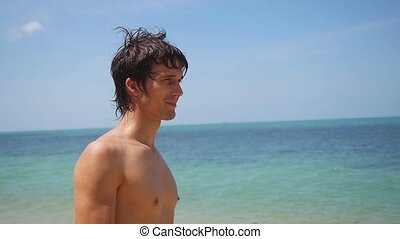 Young handsome tan man standing on the beach enjoying sunny...