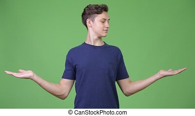 Young handsome teenage boy comparing - Studio shot of young...