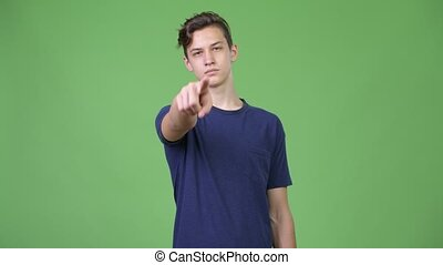 Young handsome teenage boy pointing to camera
