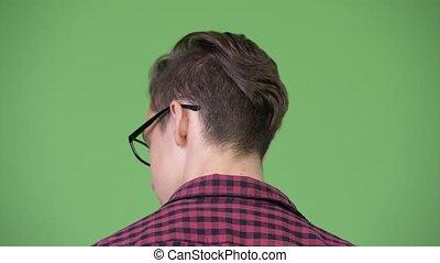 Young handsome teenage nerd boy looking back