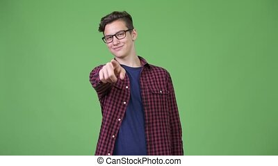 Young handsome teenage nerd boy pointing to camera
