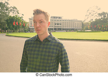 Young handsome tourist man exploring Ho Chi Minh city in Vietnam