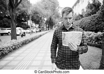 Young handsome tourist man looking at the map in the city streets