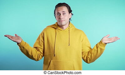 Young handsome unsure guy in yellow hoodie shrugs his arms, makes gesture of I don't know, can't help anything.