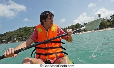 Young handsome wet man paddling on kayak boat in the sea in...