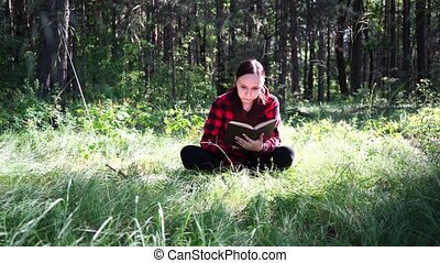 Young handsome woman reading book in open space - Young...