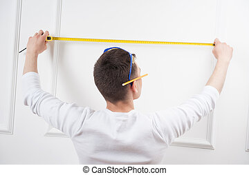 Young handsome worker with measuring tape