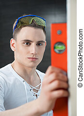 Young handsome worker with spirit level - Young caucasian ...