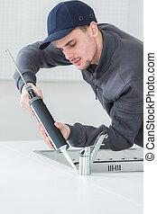 young handyman applying silicone sealant with gun around sink