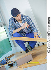 young handyman fitting wooden floor at construction site