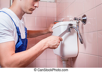 Young handyman fixing a toilet - Plumber repairing a toilet...