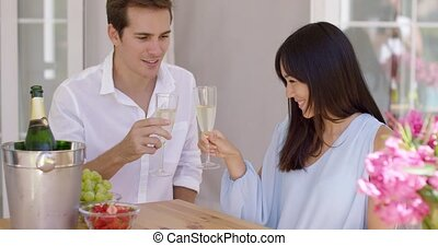 Young happy adult couple toasting champagne glasses in...