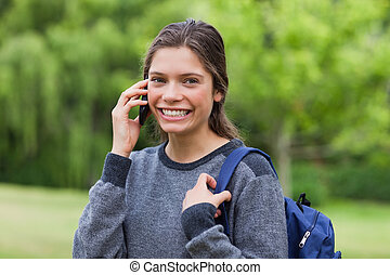 Young happy adult using her mobile phone while standing upright in the countryside