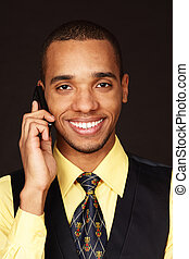 Young happy african-american businessman talking on phone