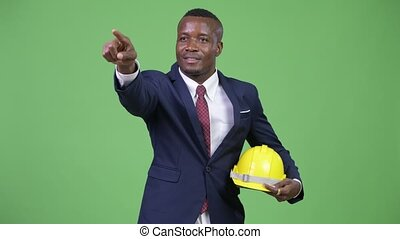Young happy African businessman as engineer directing -...