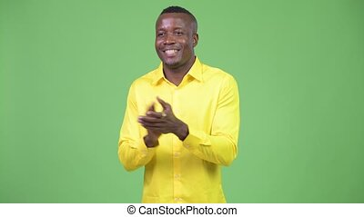 Young happy African businessman clapping hands