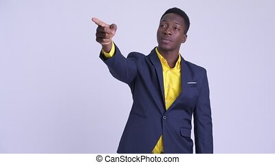 Young happy African businessman directing and pointing...