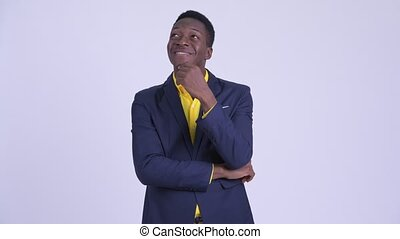 Young happy African businessman in suit thinking