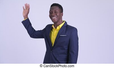 Young happy African businessman in suit waving hand