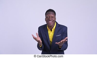 Young happy African businessman looking surprised