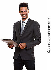 Young happy African businessman smiling while holding clipboard