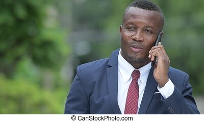 Young happy African businessman thinking while talking on the phone outdoors