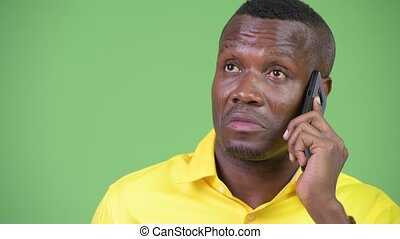 Young happy African businessman thinking while talking on the phone