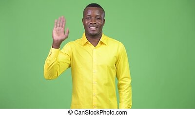 Young happy African businessman waving hand