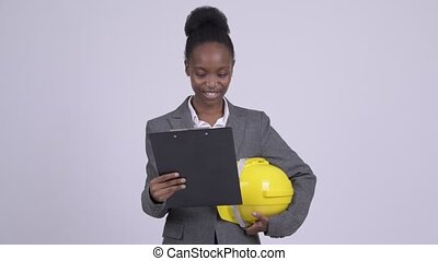 Young happy African businesswoman holding hardhat while...