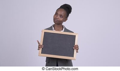 Young happy African businesswoman thinking while holding blackboard