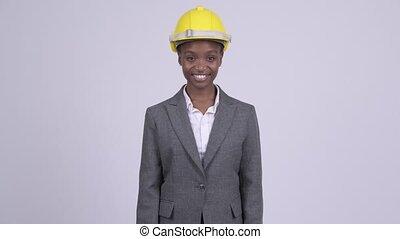 Young happy African businesswoman wearing hardhat - Studio...