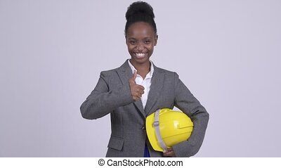 Young happy African businesswoman with hardhat giving thumbs...
