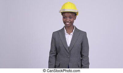 Young happy African businesswoman with hardhat thinking -...