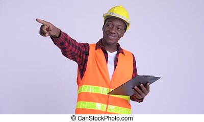Young happy African man construction worker directing while...