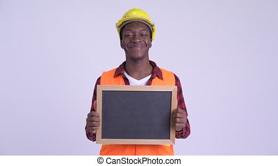 Young happy African man construction worker holding blackboard