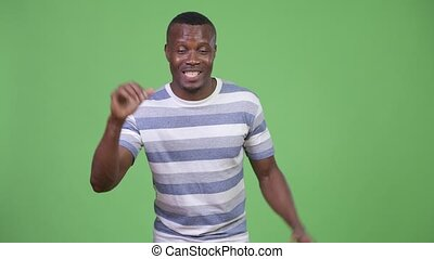 Young happy African man getting good news - Studio shot of...