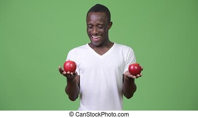 Young happy African man smiling with red apples - Studio...