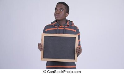 Young happy African man thinking while holding blackboard