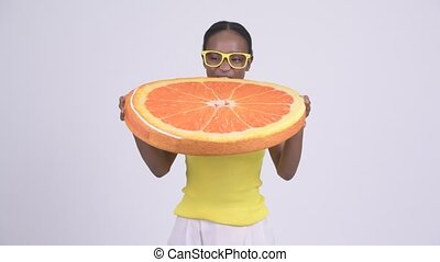 Young happy African woman biting orange pillow as healthy...