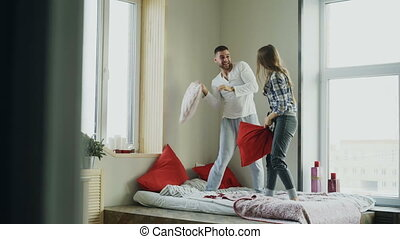 Young happy and loving couple fight pillows in bed at home...