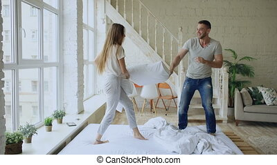 Young happy and loving couple having pillow fight and...