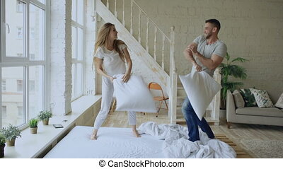 Young happy and loving couple having pillow fight in bed at...