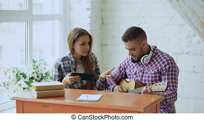 Young happy and loving couple study to play acoustic guitar...