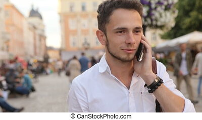 Young happy and relaxed man talking on phone in the city center.