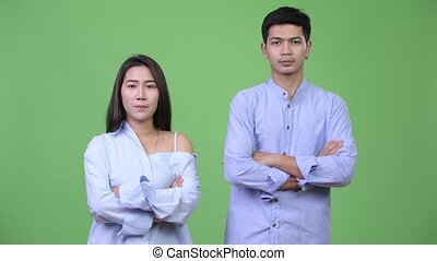 Young happy Asian business couple with arms crossed together