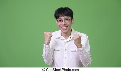 Young happy Asian businessman smiling and excited